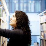 En student letar i bibliotekets bokhyllor