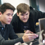 Två studenter vid en bärbar dator
